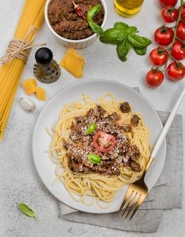 Тарелка с спагетии болоньезе со столовыми приборами