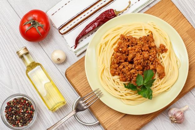 スパゲッティボロネーゼと料理の材料を盛り付けます。オールスパイスペッパー、オイルのボトル、ニンニク、唐辛子、トマトの入ったガラスのボウル。上面図。