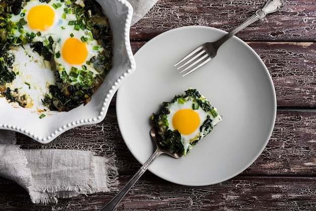 Plate with spinach and egss on table