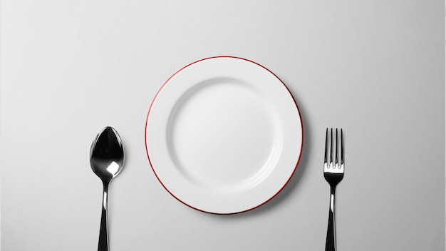 Plate with spoon and fork on white table _isolated background stock photograph