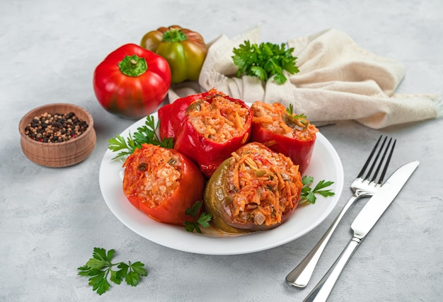 A plate with stewed stuffed peppers with fresh herbs on a gray background