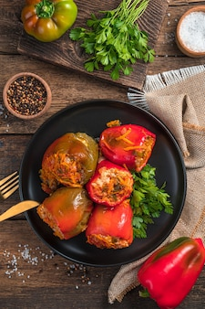 A plate with stuffed peppers and herbs on a wooden background