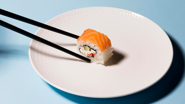 Plate with sushi roll and chopsticks