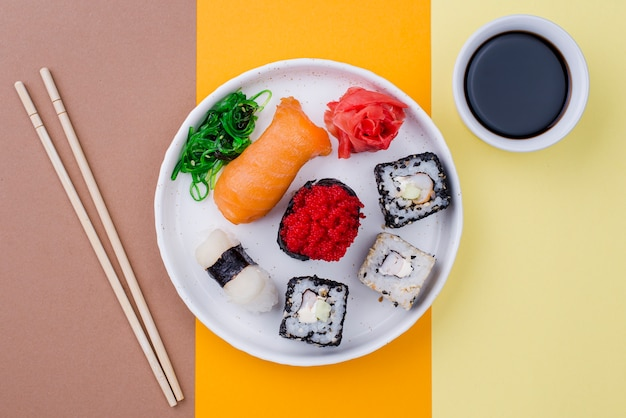 Plate with sushi and souce on table