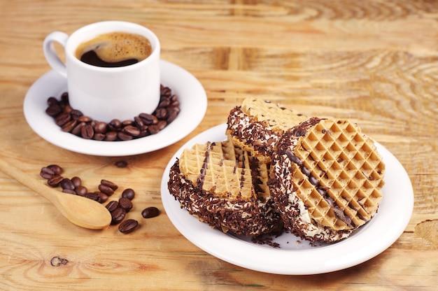 古い木製のテーブルに甘いチョコレートケーキとホットコーヒーのカップでプレート
