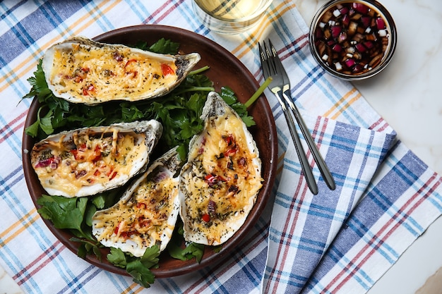 Plate with tasty baked oysters on table