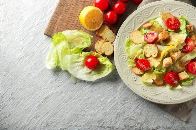 Plate with tasty caesar salad on table
