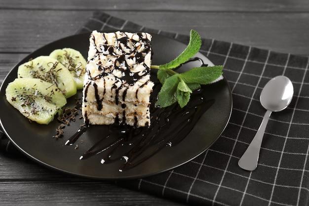 Тарелка с вкусным тортом и шоколадным соусом на деревянном столе, крупным планом