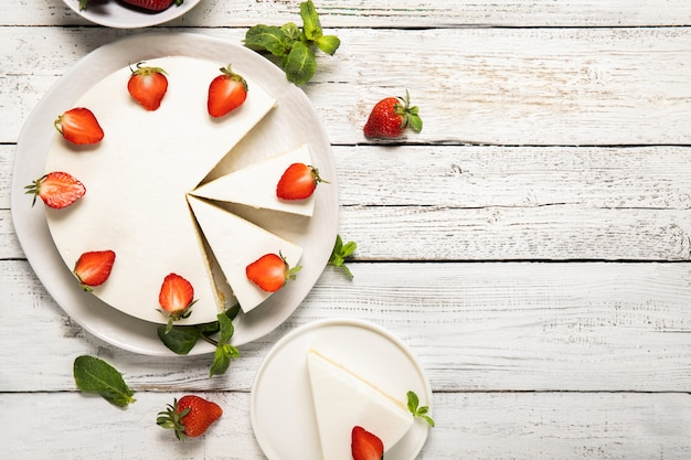 Plate with tasty cheesecake with strawberries and mint on a wooden background. view from above
