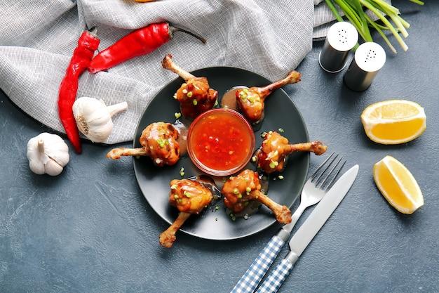 어두운 표면에 맛있는 치킨 막대 사탕과 접시