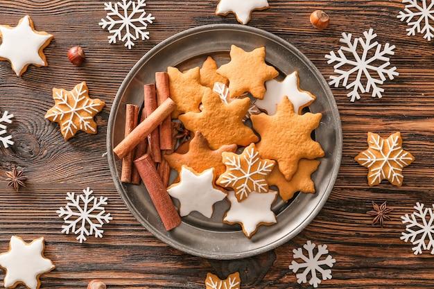 Тарелка с вкусным рождественским печеньем на деревянном столе