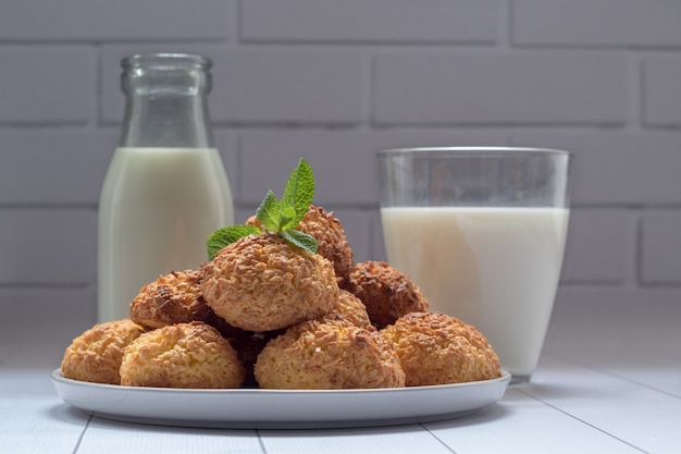 Plate with tasty coconut cookies and milk on white wooden table