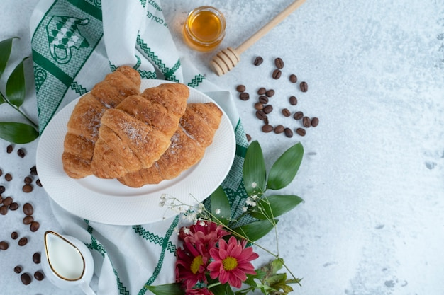 Plate with tasty croissants and aroma coffee beans .