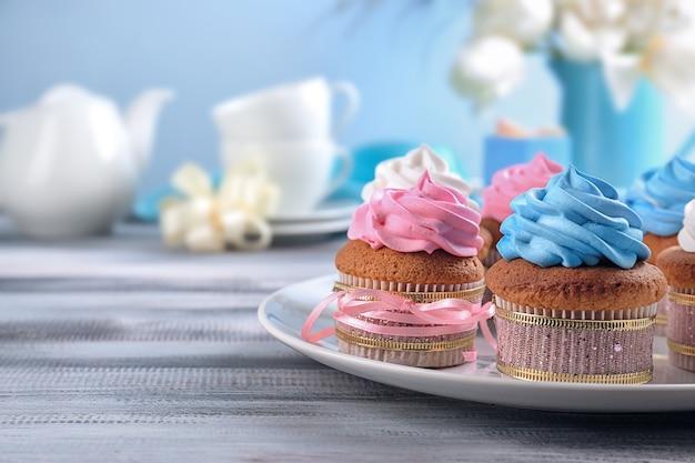 테이블에 맛있는 컵 케이크와 접시입니다. 어머니의 날 축하