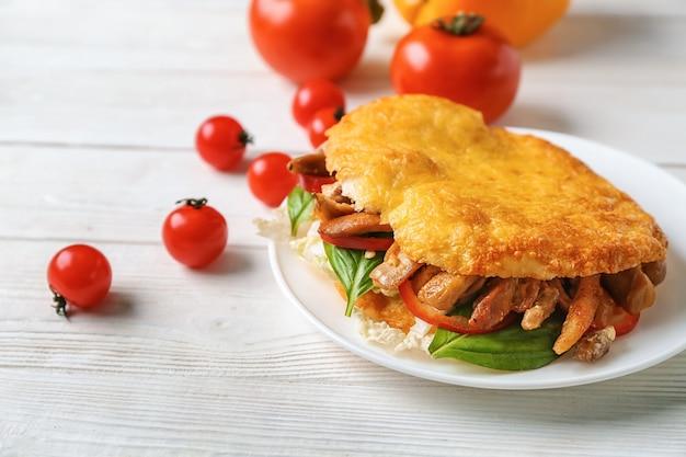 Тарелка с вкусным донер-кебабом на белом деревянном столе