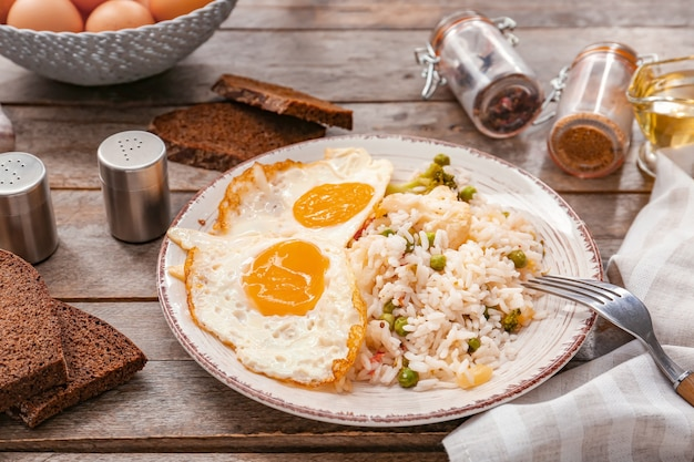 Plate with tasty eggs, vegetables and rice on wooden
