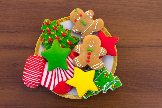 Plate with tasty festive christmas cookies in the shape of christmas tree, gingerbread man, star and christmas sock on wooden table. top view