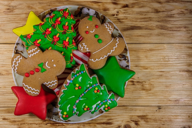 Plate with tasty festive christmas gingerbread cookies in the shape of christmas tree, gingerbread man, star and christmas stocking on wooden table. top view