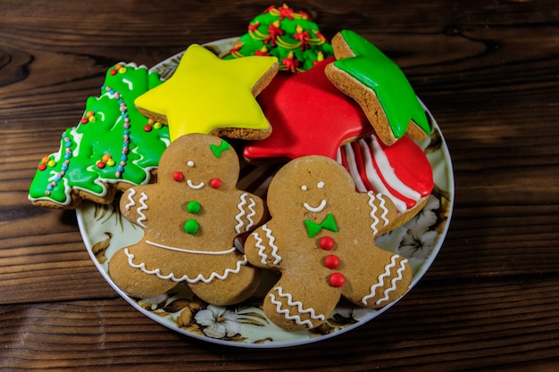 Plate with tasty festive christmas gingerbread cookies in the shape of christmas tree, gingerbread man, star and christmas stocking on wooden table