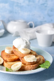 Plate with tasty french toasts, banana and ice cream on table