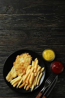 Тарелка с вкусной жареной рыбой и жареным картофелем