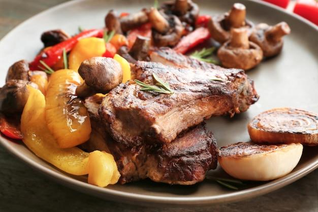 테이블에 맛있는 구운 스테이크와 야채 접시를 닫습니다.