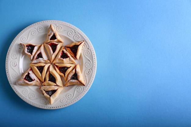 색상 배경에 purim 휴가를위한 맛있는 hamantaschen 플레이트