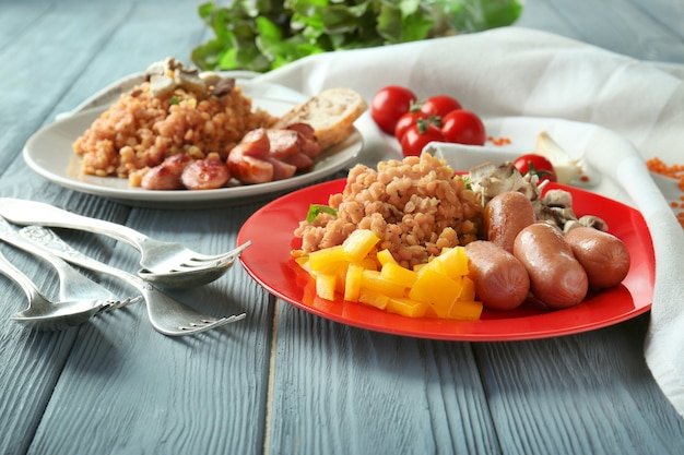 Plate with tasty lentils, sausages and vegetables on table