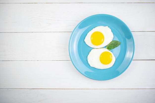 Тарелка с вкусными овсяными хлопьями, ломтиками банана и яичницей на белом дереве