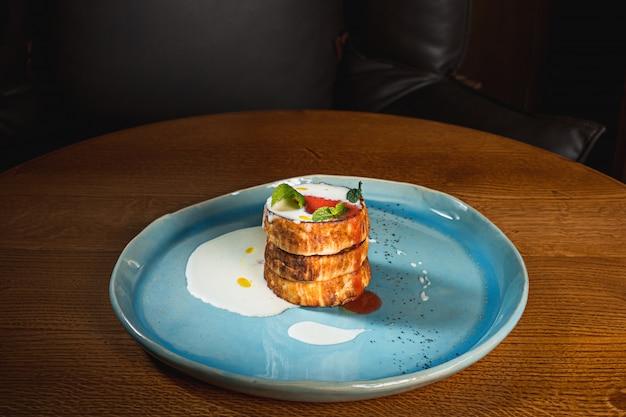 Тарелка с вкусными блинами на деревянном столе