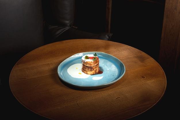 Тарелка с вкусными блинами на деревянный стол