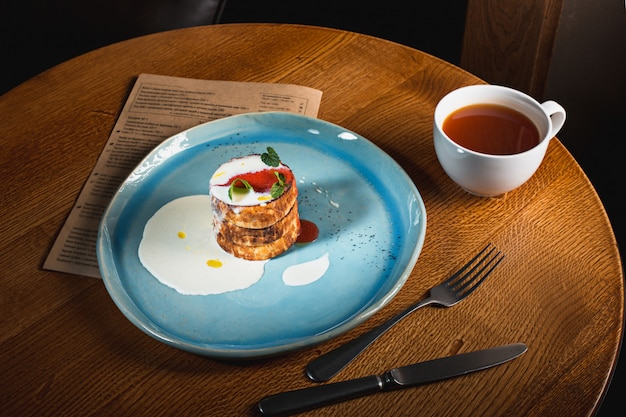 Plate with tasty pancakes on wooden table