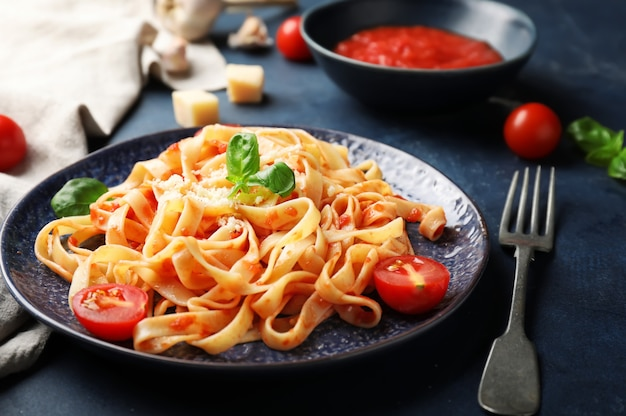 Plate with tasty pasta and tomato sauce on dark background