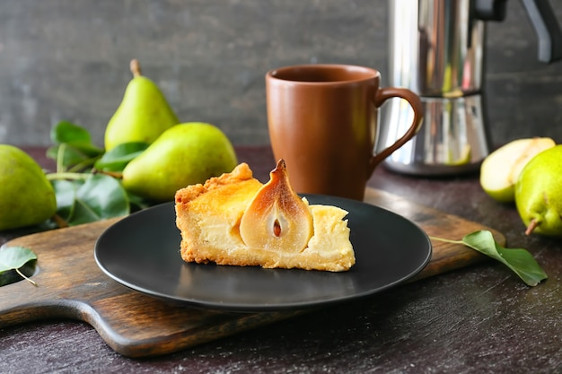 Plate with tasty pear cake on table