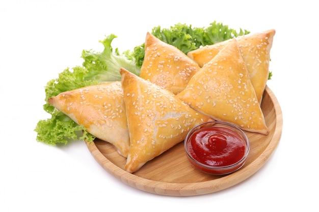 Plate with tasty samsa and sauce