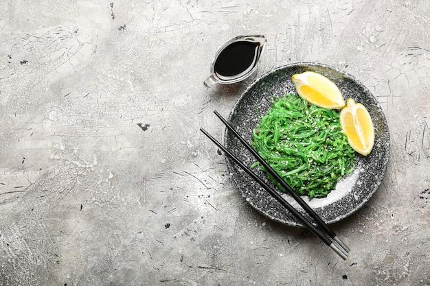 Тарелка с вкусным салатом из морских водорослей на сером фоне