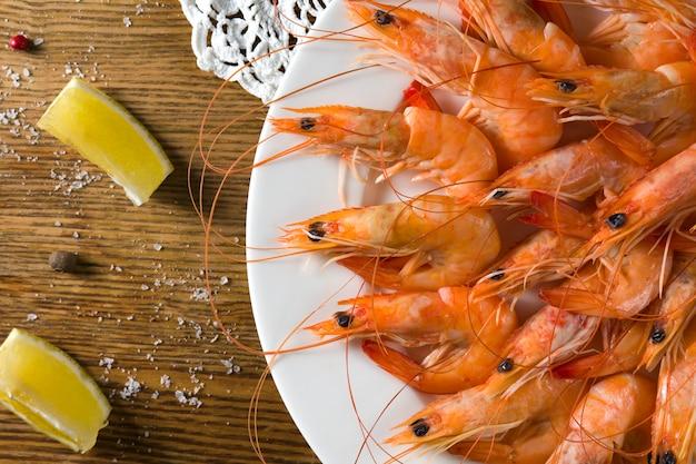 白いプレートにレモンとおいしいエビのプレートは、手作りのテーブルクロスと古いスタイルのテーブルで提供しています。上面図
