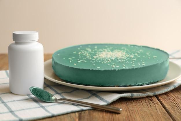 Тарелка с вкусным чизкейком со спирулиной на столе