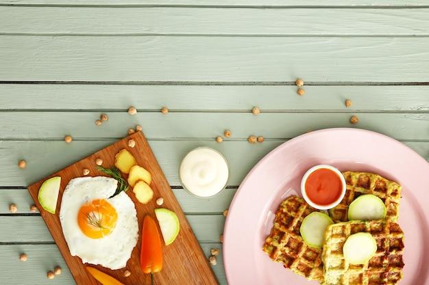 木製のテーブルにおいしいスカッシュワッフル、ソース、目玉焼きを盛り付けます