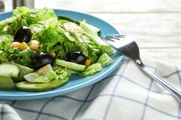 Тарелка с вкусным овощным салатом на столе, крупным планом