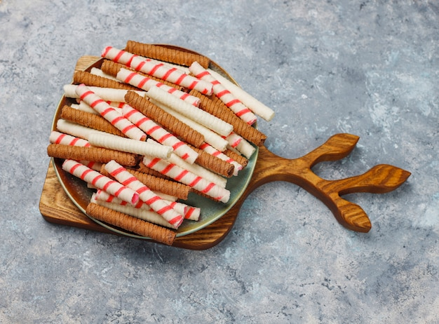 Plate with tasty wafer roll sticks on concrete surface