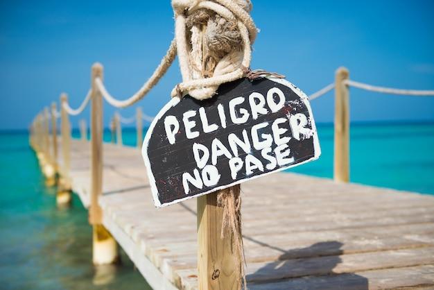 古い木製の桟橋に危険の碑文が書かれたプレート。