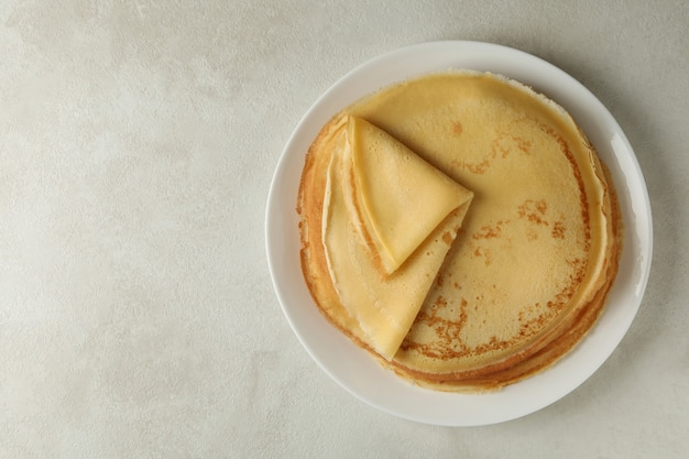 Plate with thin pancakes on white textured background