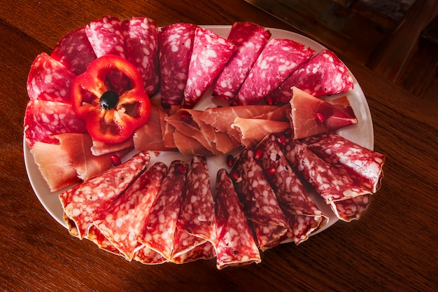 Plate with thinly sliced jamon and salami slices rolled up and decorated with a slice of red lettuce pepper