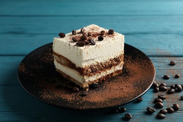 Тарелка с тирамису на деревянных фоне. вкусный десерт