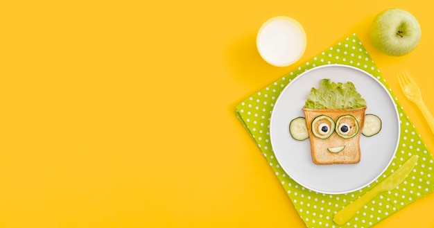 Plate with toast face shape with apple with copy-space