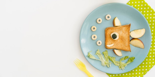 Plate with toast in fish shape with apple with copy-space