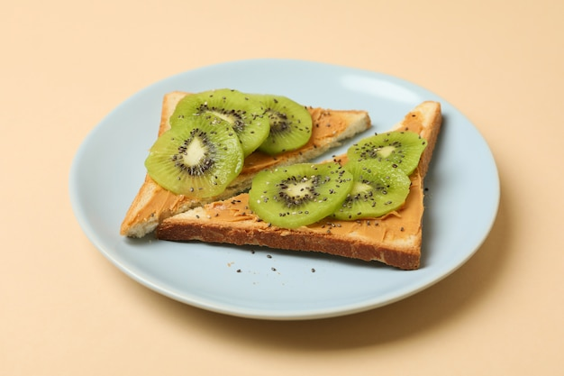 Plate with toasts with kiwi on beige background
