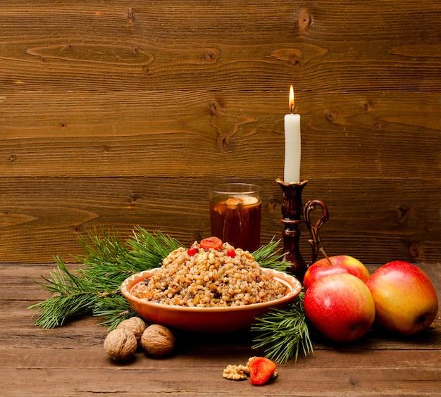 クリスマスイブに伝統的なクリスマスの御馳走スラブ人とプレート。木製の背景にコンポート、トウヒの枝、リンゴ、キャンドル。テキスト用のスペース