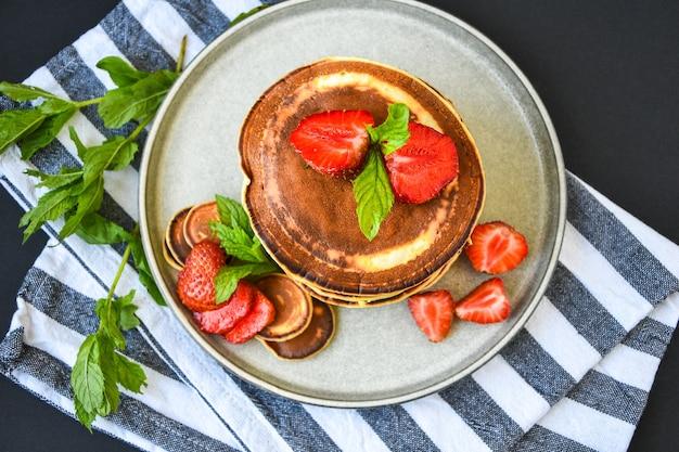 暗い背景にイチゴとミントの葉を添えた伝統的なパンケーキと小さなパンケーキシリアルのプレート。トレンディな料理。ミニシリアルパンケーキ